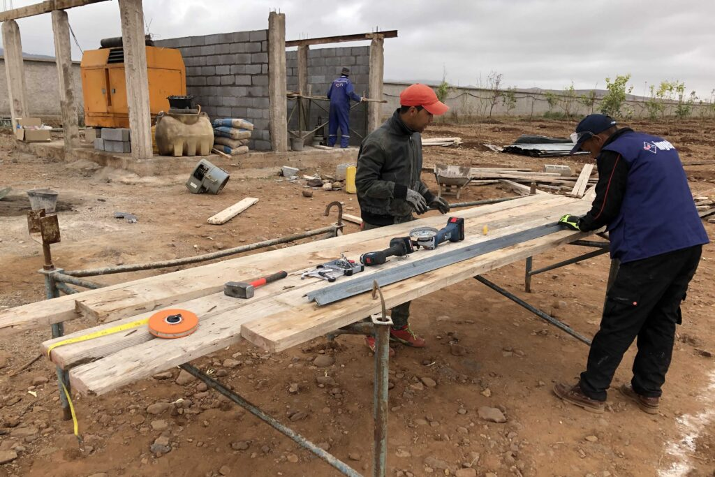 Local team working on inverter shack and PV mounting structures